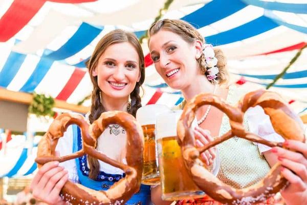2-friends-in-classic-german-attire-enjoying-pretzels-at-oktoberfest-in-Helen-GA.-