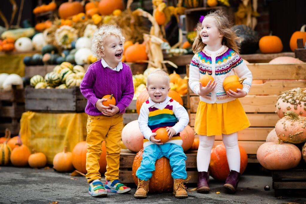 Happy Children Holding Pumpkins For Oktoberfest