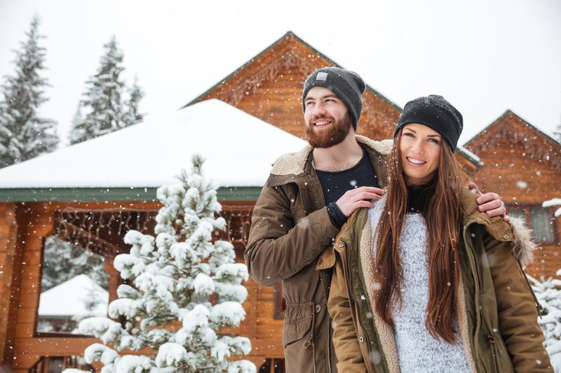 Couple Standing In Front Of Cabin Covered In Snow